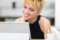 Γυναίκα που χαμογελά σε μια οθόνη υπολογιστή Στοκ φωτογραφία με δικαίωμα ελεύθερης χρήσης