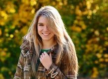 Γυναίκα που χαμογελά στο πάρκο φθινοπώρου Στοκ φωτογραφία με δικαίωμα ελεύθερης χρήσης