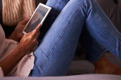 Γυναίκα που χαλαρώνει στο σπίτι να χρησιμοποιήσει την ψηφιακή ταμπλέτα, χαμηλή συγκομιδή τμημάτων Στοκ φωτογραφία με δικαίωμα ελεύθερης χρήσης