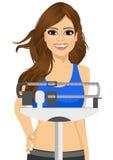 Γυναίκα που χρησιμοποιεί έναν ζυγό για να μετρήσει το βάρος της Στοκ Εικόνα
