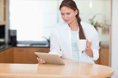 Γυναίκα που χρησιμοποιεί έναν υπολογιστή ταμπλετών πίνοντας το τσάι στοκ φωτογραφία με δικαίωμα ελεύθερης χρήσης