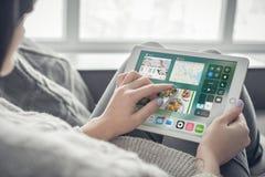 Γυναίκα που χρησιμοποιεί ένα ολοκαίνουργιο υπέρ ασήμι της Apple iPad Στοκ Εικόνες