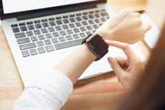 Γυναίκα που χρησιμοποιεί ένα ψηφιακό ρολόι στις προόδους επίδειξης και τεχνολογίας στην επικοινωνία Αυτό είναι μια νέα τεχνολογία στοκ φωτογραφία