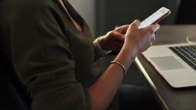 Γυναίκα που χρησιμοποιεί ένα smartphone με το lap-top στο υπόβαθρο φιλμ μικρού μήκους