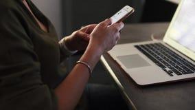 Γυναίκα που χρησιμοποιεί ένα smartphone με το lap-top στο υπόβαθρο απόθεμα βίντεο