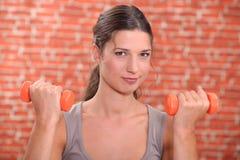 Γυναίκα που χρησιμοποιεί τα βάρη χεριών Στοκ Φωτογραφίες