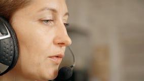 Γυναίκα που χρησιμοποιεί την κάσκα και το μικρόφωνο στην εργασία στο τηλεφωνικό κέντρο ser απόθεμα βίντεο