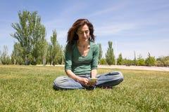Γυναίκα που χρησιμοποιεί την κινητή τηλεφωνική συνεδρίαση στο πάρκο Στοκ φωτογραφίες με δικαίωμα ελεύθερης χρήσης