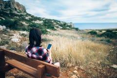 Γυναίκα που χρησιμοποιεί την κινητή τηλεφωνική συνεδρίασή της σε έναν πάγκο στο όμορφο val Στοκ Φωτογραφία