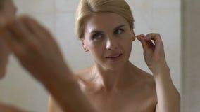 Γυναίκα που χρησιμοποιεί την πατσαβούρα βαμβακιού για να καθαρίσει τα αυτιά της στο λουτρό, υγιεινή αυτιών, υγειονομική περίθαλψη απόθεμα βίντεο