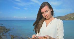Γυναίκα που χρησιμοποιεί την πιστωτική κάρτα στις διακοπές που ψωνίζουν on-line με το κινητό τηλέφωνο στο σαφές μπλε υπόβαθρο θάλ φιλμ μικρού μήκους