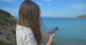 Γυναίκα που χρησιμοποιεί την πιστωτική κάρτα στις διακοπές που ψωνίζουν on-line με το κινητό τηλέφωνο στο σαφές μπλε υπόβαθρο θάλ απόθεμα βίντεο