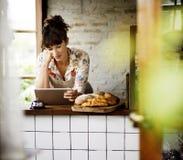 Γυναίκα που χρησιμοποιεί την ταμπλέτα για τη σε απευθείας σύνδεση επιχειρησιακή διαταγή Στοκ Εικόνα