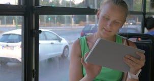 Γυναίκα που χρησιμοποιεί την ταμπλέτα στο λεωφορείο απόθεμα βίντεο