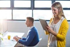 Γυναίκα που χρησιμοποιεί την ψηφιακή ταμπλέτα από το συνάδελφο στην αρχή στοκ εικόνες με δικαίωμα ελεύθερης χρήσης