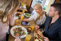 Γυναίκα που χρησιμοποιεί την ψηφιακή ταμπλέτα ενώ έχοντας το γεύμα με Στοκ εικόνα με δικαίωμα ελεύθερης χρήσης