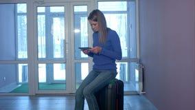 Γυναίκα που χρησιμοποιεί την ψηφιακή ταμπλέτα καθμένος στη βαλίτσα στο λόμπι απόθεμα βίντεο