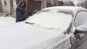 Γυναίκα που χρησιμοποιεί τη βούρτσα κοντά στο χιονισμένο αυτοκίνητο φιλμ μικρού μήκους