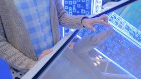 Γυναίκα που χρησιμοποιεί τη διαλογική επίδειξη οθονών επαφής στην έκθεση τεχνολογίας φιλμ μικρού μήκους