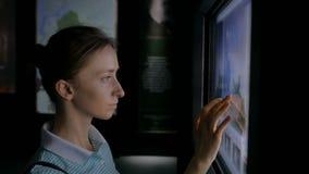 Γυναίκα που χρησιμοποιεί τη διαλογική επίδειξη οθονών επαφής στο μουσείο σύγχρονης ιστορίας απόθεμα βίντεο