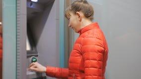Γυναίκα που χρησιμοποιεί τη μηχανή μετρητών Ελκυστικό νέο θηλυκό στο κόκκινο σακάκι φυσαλίδων που παρεμβάλλει την πιστωτική κάρτα φιλμ μικρού μήκους