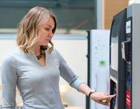 Γυναίκα που χρησιμοποιεί τη μηχανή πώλησης καφέ στοκ εικόνα με δικαίωμα ελεύθερης χρήσης