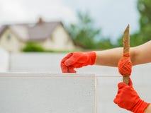 Γυναίκα που χρησιμοποιεί τη σειρά ως επίπεδο στην κατασκευή τοίχων στοκ εικόνα