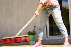 Γυναίκα που χρησιμοποιεί τη σκούπα για να καθαρίσει επάνω το patio κατωφλιών Στοκ Εικόνες