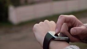 Γυναίκα που χρησιμοποιεί τη συσκευή οθονών επαφής smartwatch της σε ένα υπόβαθρο επαρχίας 4k απόθεμα βίντεο
