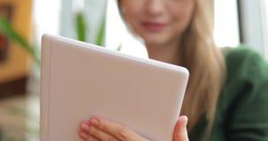 Γυναίκα που χρησιμοποιεί τη συσκευή PC ταμπλετών στον καφέ απόθεμα βίντεο