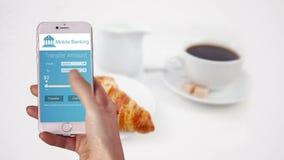 Γυναίκα που χρησιμοποιεί τις κινητές τραπεζικές εργασίες στο τηλέφωνό της απόθεμα βίντεο