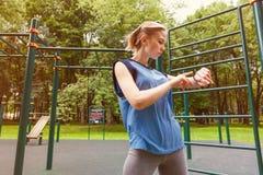Γυναίκα που χρησιμοποιεί τον ιχνηλάτη δραστηριότητας στη γυμναστική Στοκ φωτογραφία με δικαίωμα ελεύθερης χρήσης