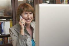 Γυναίκα που χρησιμοποιεί τον υπολογιστή και το κινητό τηλέφωνο στο δωμάτιο μελέτης Στοκ Εικόνες