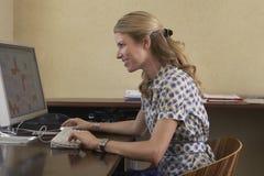 Γυναίκα που χρησιμοποιεί τον υπολογιστή στην αρχή στοκ εικόνα