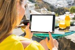 Γυναίκα που χρησιμοποιεί τον υπολογιστή ταμπλετών ενώ έχοντας το πρόγευμα, Στοκ Φωτογραφία