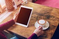 Γυναίκα που χρησιμοποιεί τον υπολογιστή ταμπλετών στη καφετερία Στοκ Φωτογραφίες