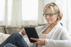 Γυναίκα που χρησιμοποιεί τον υπολογιστή ταμπλετών στον καναπέ Στοκ φωτογραφία με δικαίωμα ελεύθερης χρήσης