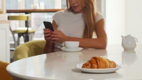 Γυναίκα που χρησιμοποιεί το έξυπνο τηλέφωνο στον καφέ αρτοποιείων, εύγευστος croissant στο πρώτο πλάνο απόθεμα βίντεο