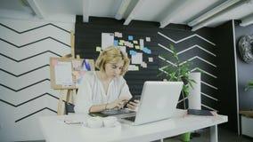 Γυναίκα που χρησιμοποιεί το έξυπνο τηλέφωνο στο σύγχρονο γραφείο απόθεμα βίντεο