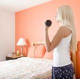 Γυναίκα που χρησιμοποιεί το βάρος βραχιόνων στην κρεβατοκάμαρα Στοκ Εικόνες