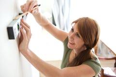 Γυναίκα που χρησιμοποιεί το επίπεδο και το μολύβι πνευμάτων για να χαρακτηρίσει τον τοίχο στοκ εικόνες