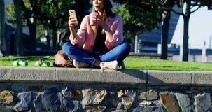 Γυναίκα που χρησιμοποιεί το κινητό τηλέφωνο ενώ έχοντας το χυμό 4k απόθεμα βίντεο
