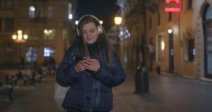Γυναίκα που χρησιμοποιεί το κινητό τηλέφωνο κατά τη διάρκεια του περιπάτου στις οδούς απόθεμα βίντεο