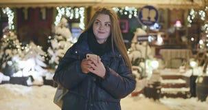 Γυναίκα που χρησιμοποιεί το κινητό τηλέφωνο κατά τη διάρκεια του περιπάτου στις οδούς της πόλης νύχτας απόθεμα βίντεο