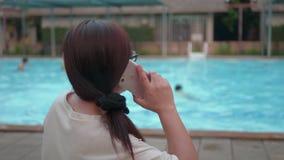 Γυναίκα που χρησιμοποιεί το κινητό τηλέφωνο κοντά στην πισίνα, που περιμένει την κόρη της φιλμ μικρού μήκους
