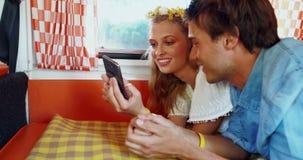 Γυναίκα που χρησιμοποιεί το κινητό τηλέφωνο μιλώντας στον άνδρα camper van 4k απόθεμα βίντεο