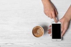 Γυναίκα που χρησιμοποιεί το κινητό τηλέφωνο στον πίνακα με το φλυτζάνι χαρτονιού του αρωματικού καφέ στοκ φωτογραφίες