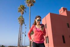 Γυναίκα που χρησιμοποιεί το κινητό τηλέφωνο στον περίπατο Benalmadena Στοκ φωτογραφία με δικαίωμα ελεύθερης χρήσης