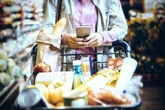 Γυναίκα που χρησιμοποιεί το κινητό τηλέφωνο ψωνίζοντας στην υπεραγορά στοκ εικόνες με δικαίωμα ελεύθερης χρήσης