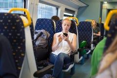 Γυναίκα που χρησιμοποιεί το κινητό τηλέφωνο διακινούμενη με το τραίνο Στοκ Εικόνες